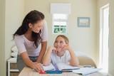 Woman assisting daughter in studies