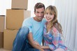 Couple sitting against cardboard boxes in new house