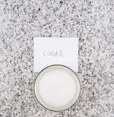 Sugar in a glass bottle on granite surface