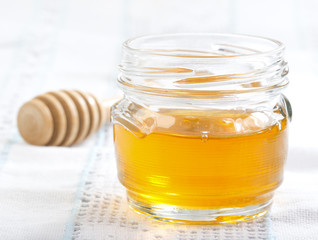Jar with honey on a white tablecloth
