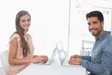 Happy young couple using laptops at table