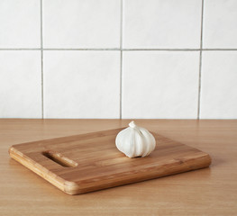 Garlic on brown cutting bamboo board used for cooking.