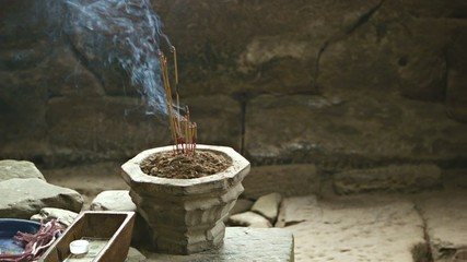 Stone bowl with incense sticks in the room of the ancient temple