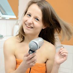 Frau trocknet Haare mit Föhn