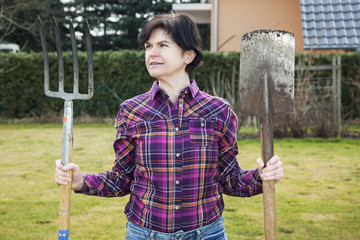 Woman with spade and fork in the garden