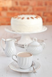 Cup of coffee with hummingbird cake on background