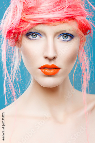 Portrait of beautiful girl with pink hair on a blue background
