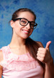 Happy girl in glasses showing thumb up sign on blue background