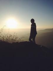 human silhouette on mountain with beautiful sunrise