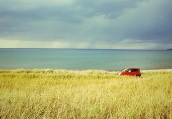 Red car in the field with sea behind