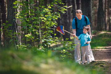 Young father and son catching butterfly in forest
