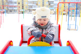 baby driving car on playground in winter