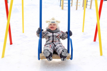 baby on seesaw in winter