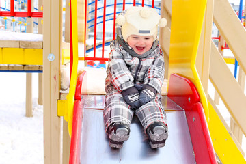funny baby on slide outdoors in winter