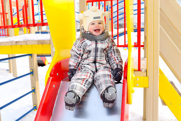 happy baby on slide outdoors