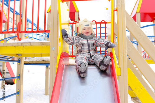 happy baby on slide in wintertime