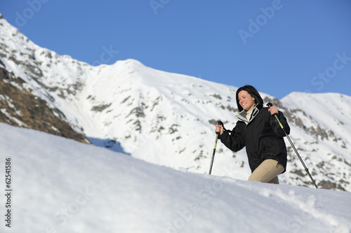 Hiker woman trekking on the snow in a snowy mountain