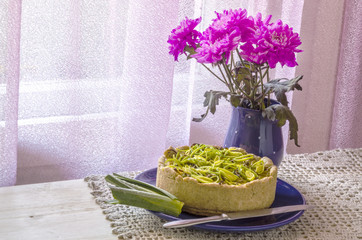 Pie quiche with leeks, cheese on linen tablecloth