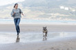 Dog and young woman running and playing in the beach.
