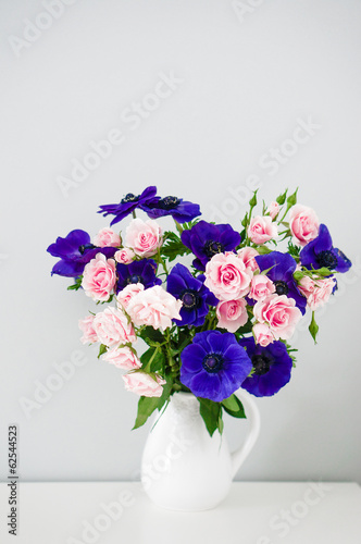 Bouquet of pink roses and blue anemones in white vase on grey ba