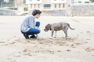 Young woman training the dog in the beach.