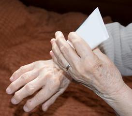 Senior woman's hands applying cream