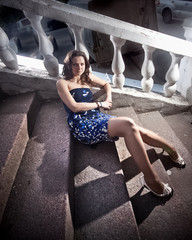 Beautiful sexy woman in blue dress lying on stone steps outdoor