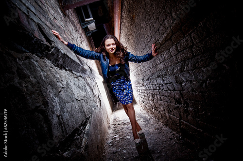 Beautiful stylish woman posing between two brick walls at night