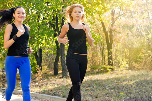 Two female friends jogging together in a park