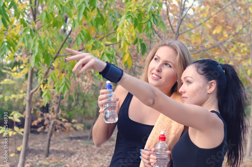Two fit young women athletes drinking water