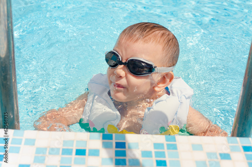 Laughing little boy climbing out of a pool
