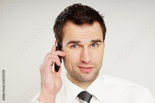 Handsome man in white shirt talks into the mobile phone