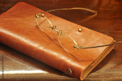 leather notebook and glasses on wooden background