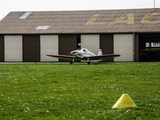 Avion devant un hangar