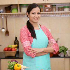 Smiling young Indian woman with kitchen apron
