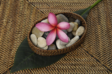 frangipani flower and stones a wicker basket on burlap texture