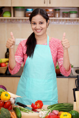 Happy young woman with kitchen apron and making thumbs up