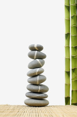 stones stack in balance with thin bamboo grove on mat