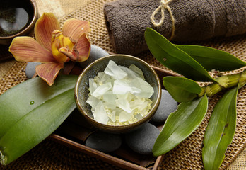 salt and orchid with towel and green leaves on mat