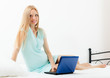 Cheerful  pregnancy woman awaking  with laptop