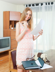 Smiling beautiful pregnant woman with documents in home interior