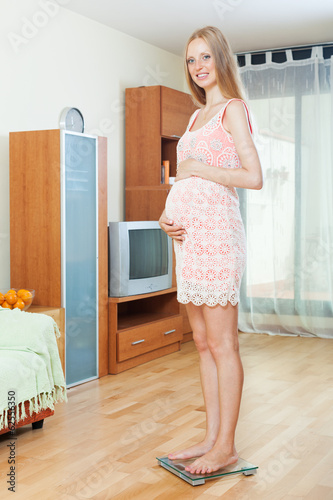 pregnancy woman weighing herself on bathroom scale