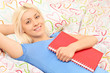 Blond girl lying in bed and holding a notebook