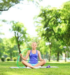 Female athlete sitting in park with exercising equipment