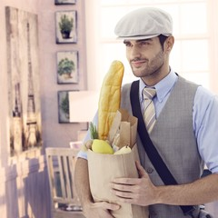 Handsome man holding grocery bag at vintage home