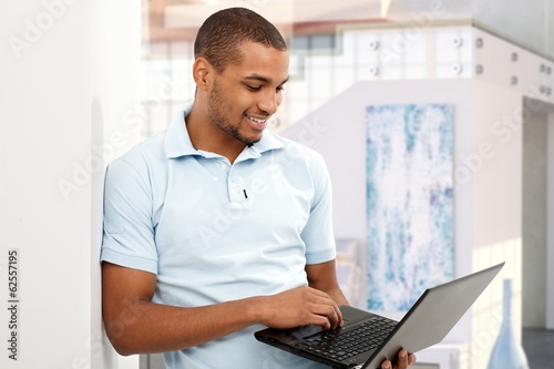 Happy afro american man with laptop computer