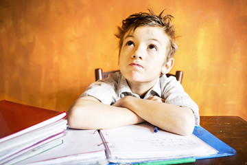 A young boy worried on homework