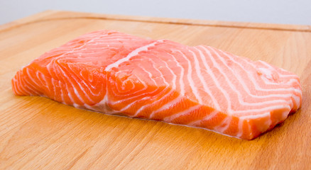 Uncooked salmon fillet on a wooden board