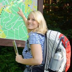 Wanderin schaut auf Wegekarte