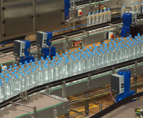 Plastic water bottles on conveyor and water bottling machine ind